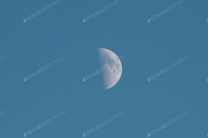 First Quarter Of Moon In Blue Sky Background