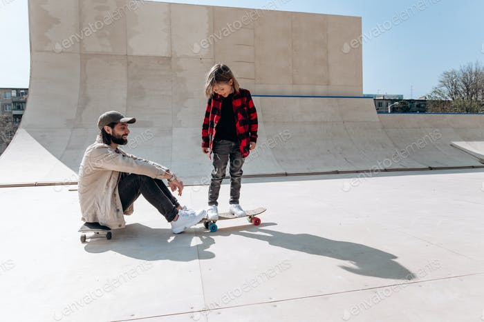 Young father sits on the skateboard and his little son stands on his skateboard in a skate park with