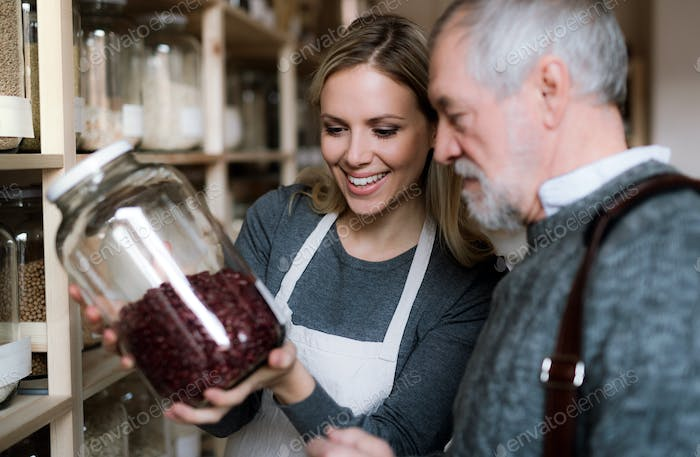 Young female shop assistant serving a senior man in a zero waste shop.