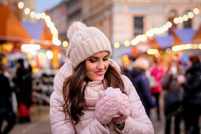 Schöne Mädchen in Winterkleidung stehen auf der Straße mit einer Messe während der Weihnachtszeit