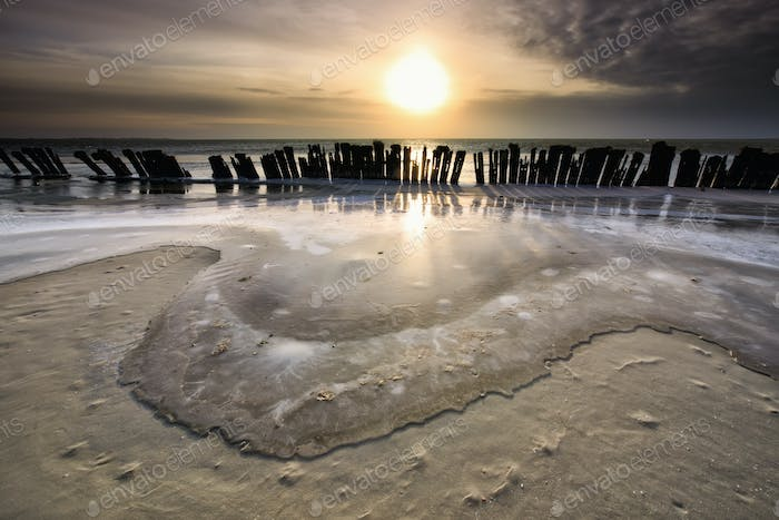 frozen waves by breakwater at sunset