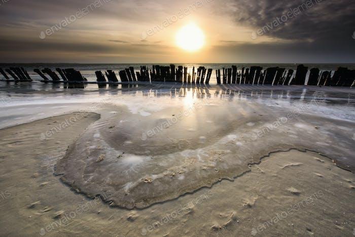 gefrorene Wellen durch Wellenbrecher bei Sonnenuntergang