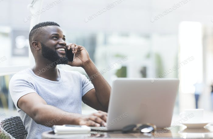 Young handsome african guy working on laptop
