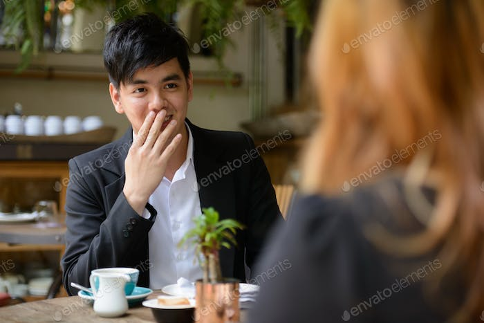 Young Asian business couple together at the coffee shop with man looking shocked