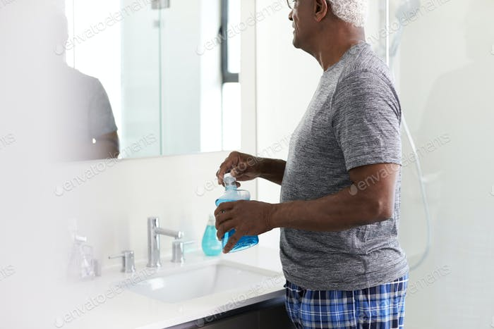 Senior Man Using Mouthwash Looking At Reflection In Bathroom Mirror Wearing Pajamas