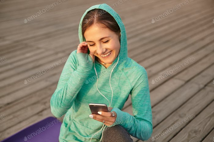 Portrait of young lady bright sportswear, listening favorite song on headphones after morning yoga
