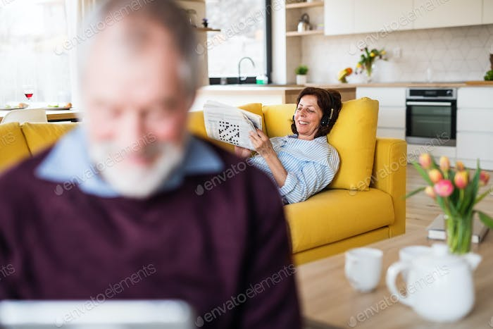 A senior couple indoors at home, relaxing