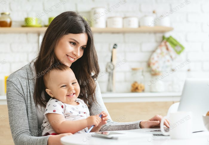 Young mom typing on laptop, sitting with baby at kitchen