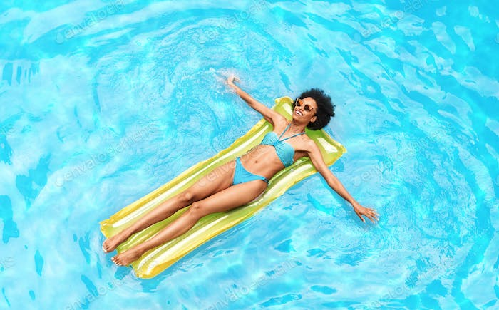 Top view of attractive black girl floating on air mattress in blue water of outdoor pool