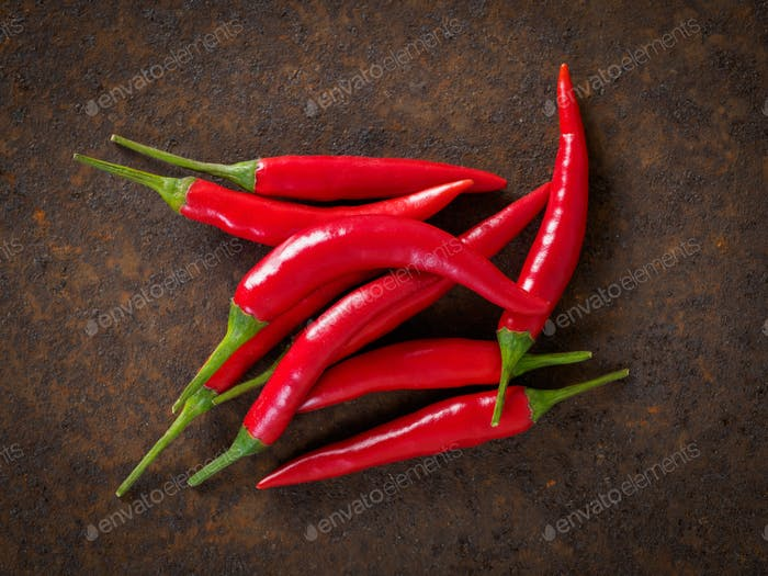 Red hot chili pepper on dark metallic rusty background, top view