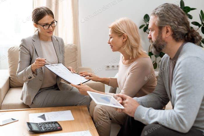 Junger Immobilienmakler zeigt auf Dokument während der Beratung von reifen Kunden
