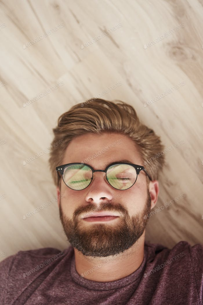 Man with glasses lying down on the floor