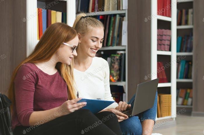 Cheerful teenage girlfriends sitting on floor in library, using laptop