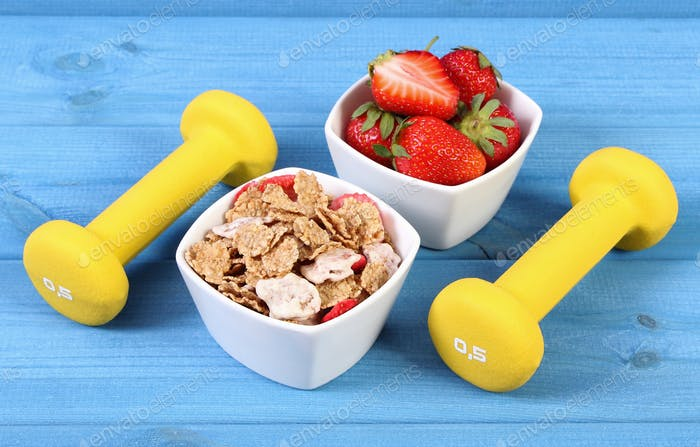 Fresh strawberries, wheat and rye flakes and dumbbells, healthy and sporty lifestyle