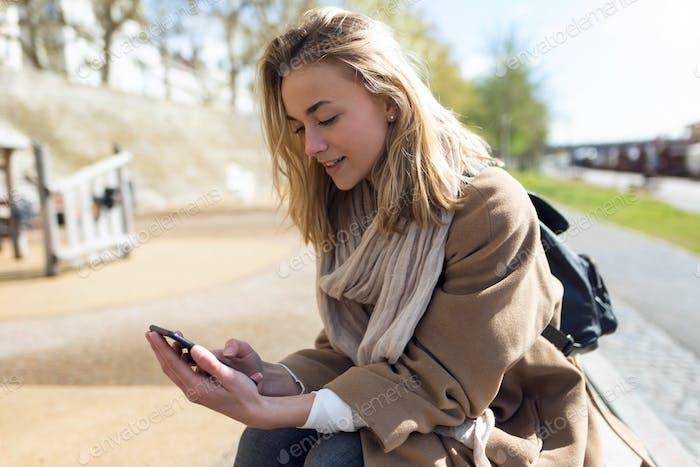 hermosa mujer joven usando su teléfono móvil junto al río i