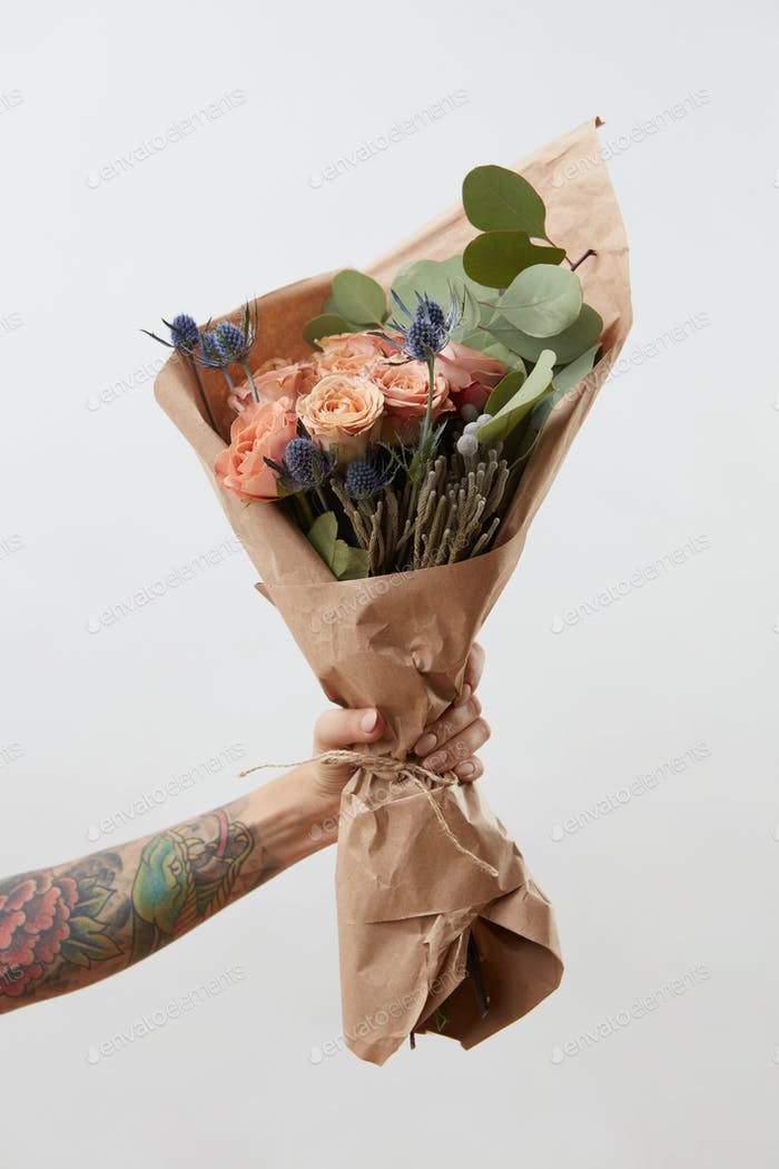 Female hand shows bouquet with rose flowers on gray background. Gift for Mother or Woman's Day