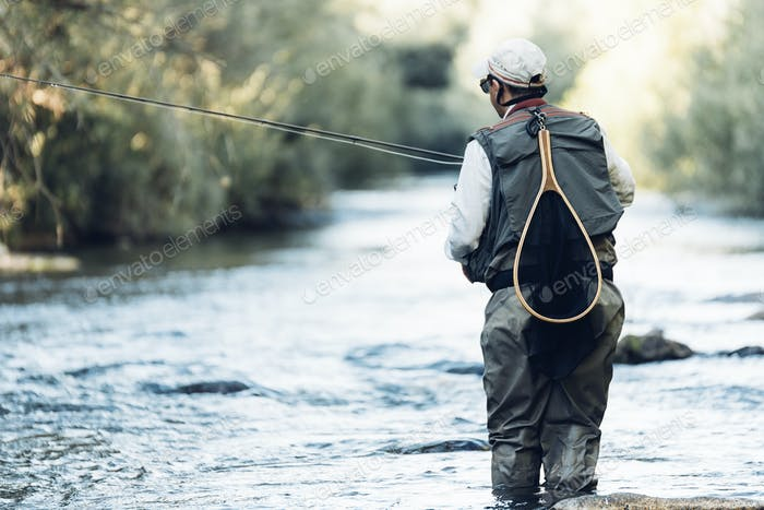 Fly fisherman using flyfishing rod.