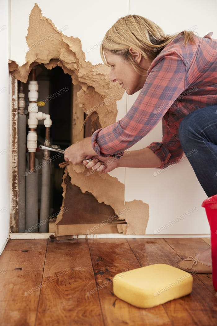 Middle aged woman repairing burst water pipe, vertical