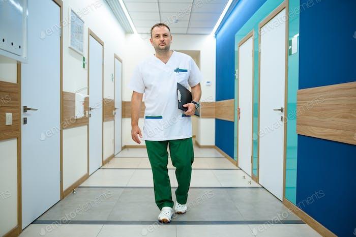 Friendly male doctor in clinic corridor