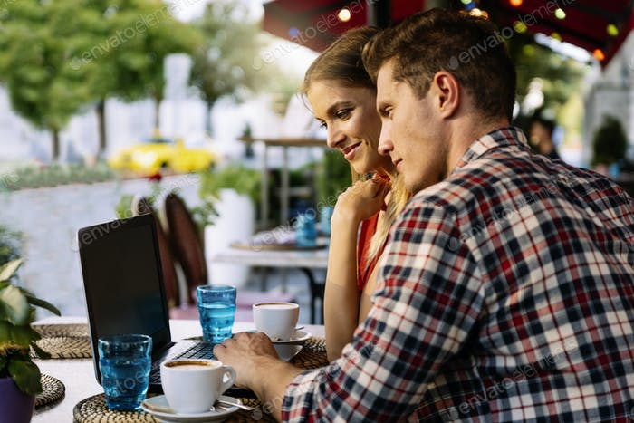 Happy couple at coffee shop using laptop.