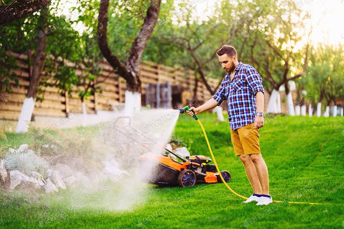 Portrait of caucasian man watering lawn in backyard using hose and water