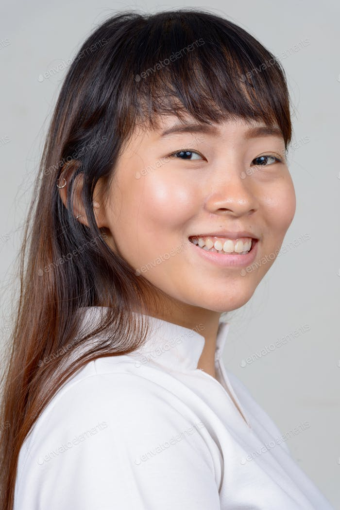Closeup profile view of happy young Asian woman looking at camera