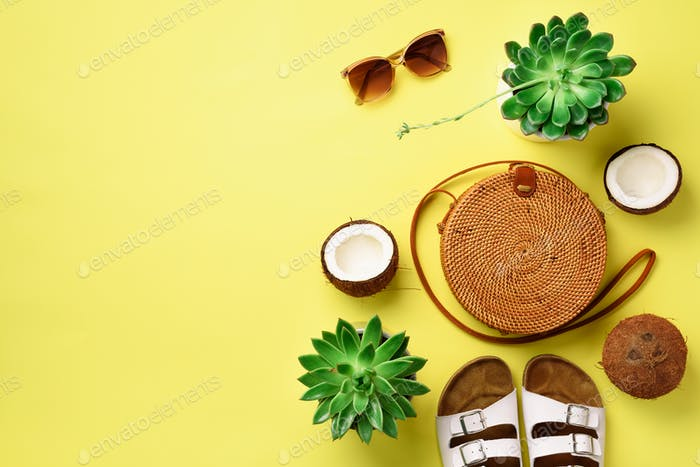 Stylish rattan bag, coconut, birkenstocks, succulent, sunglasses on yellow background. Banner. Top