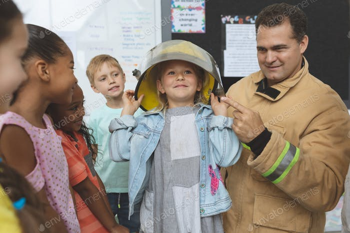 Firefighter teaching to school kids about fire security