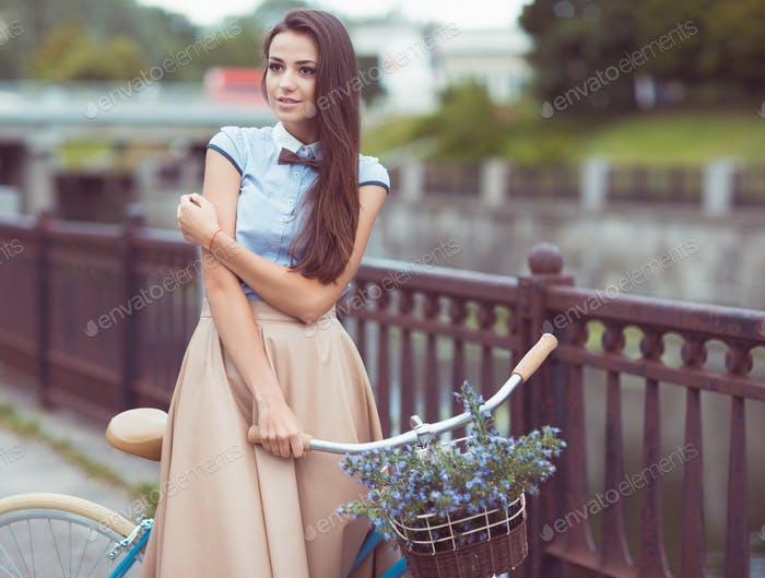 Young beautiful, elegantly dressed woman with bicycle outdoor