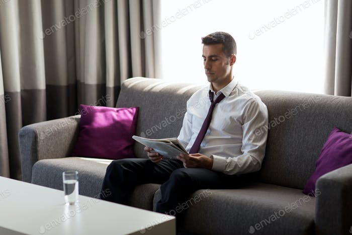 businessman reading newspaper at hotel room