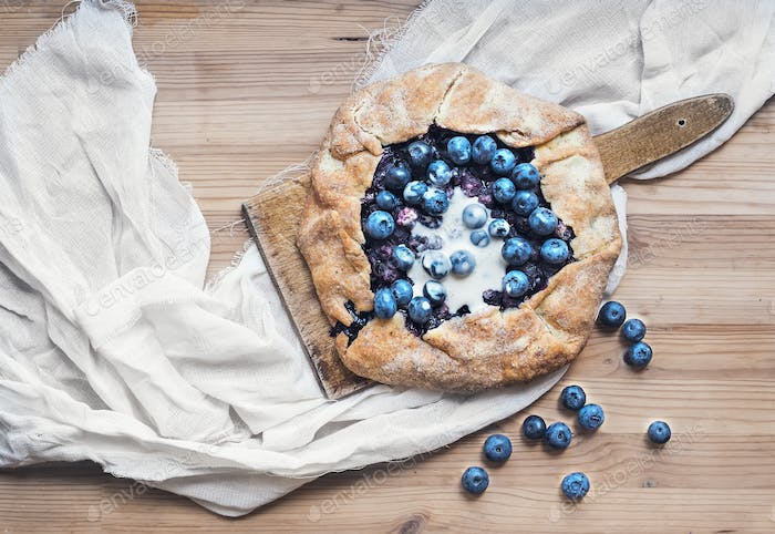 Rustic blueberry pie on a wooden board and white tissue