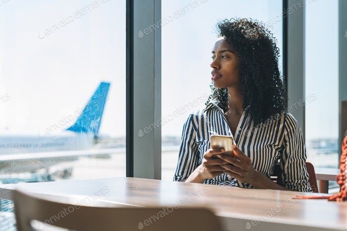 Woman on the mobile phone waiting for her flight at the airport