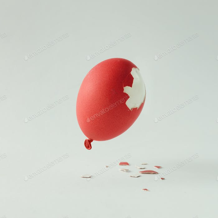 Red Easter egg balloon on bright white background. Minimal creative concept. Flat lay.