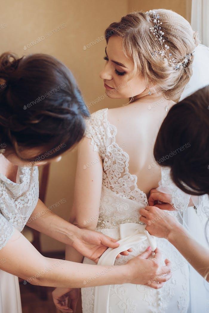 bridesmaids helping bride put on lace wedding dress