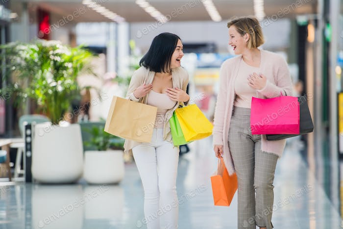 Two happy young women walking in shopping mall with shopping bags
