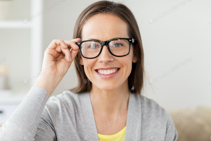 happy smiling middle aged woman in glasses at home