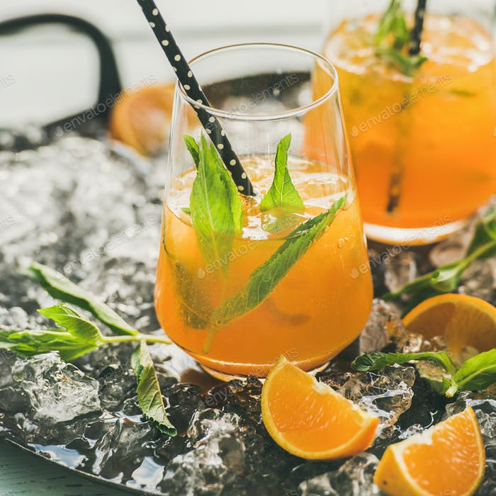 Refreshing cold alcoholic summer cocktail with orange, peppermint and ice