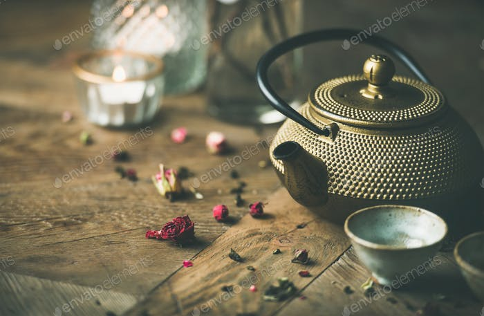 Golden iron teapot, cups, dried rose, candles over wooden background