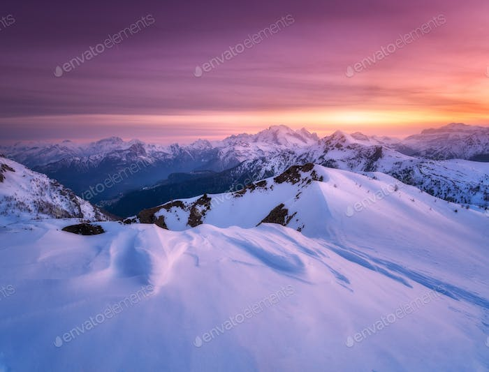 Colorful red sky and sunlight over the snow covered mountains