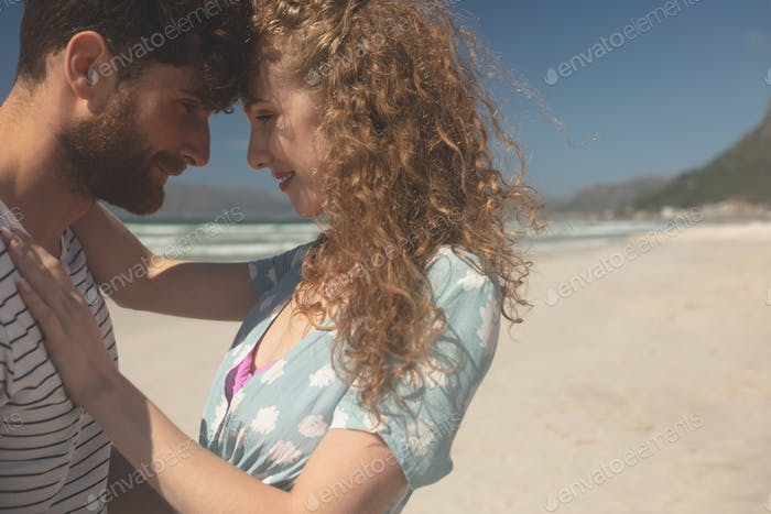 Side view of romantic Caucasian couple standing at beach on a sunny day. They are hugging each other