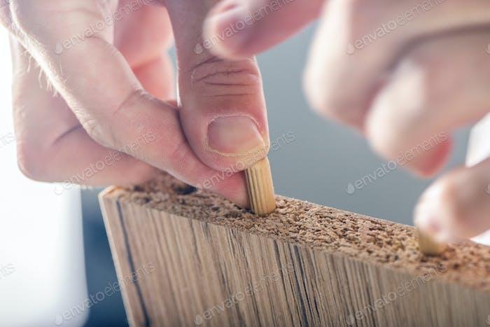 Mann Montage Möbel zu Hause, Hand mit Holzdübelstiften