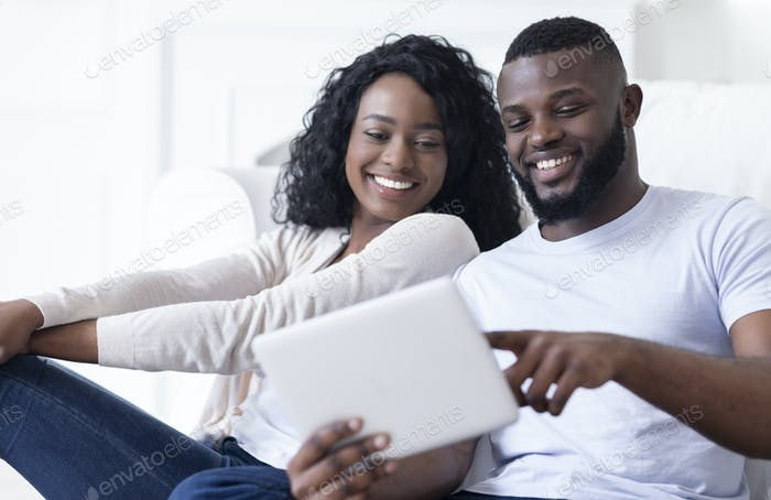 Cheerful african american couple using digital tablet watching funny videos