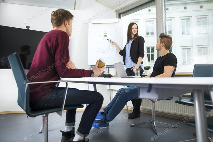 Businesswoman Explaining Graph To Coworkers In Office