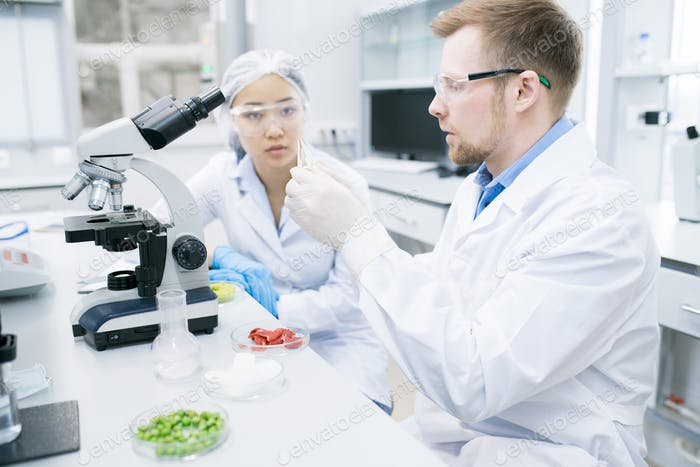 Woman scientist looking at colleague studying meat
