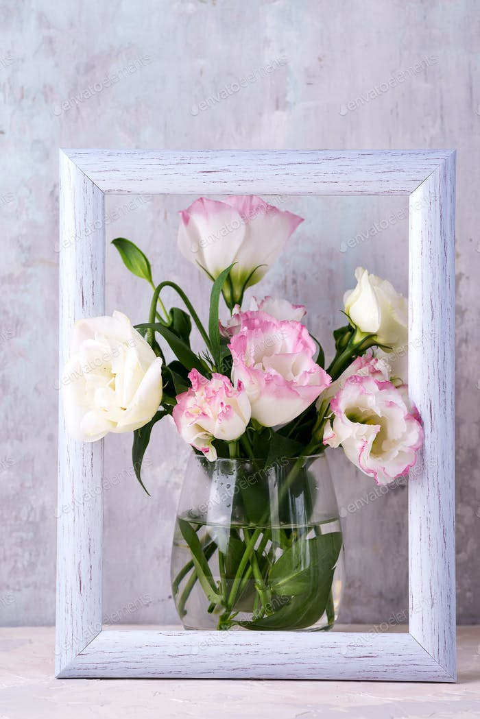 Eustoma flowers in vase in photo frame on table near stone wall, space for text. Blank for postcards