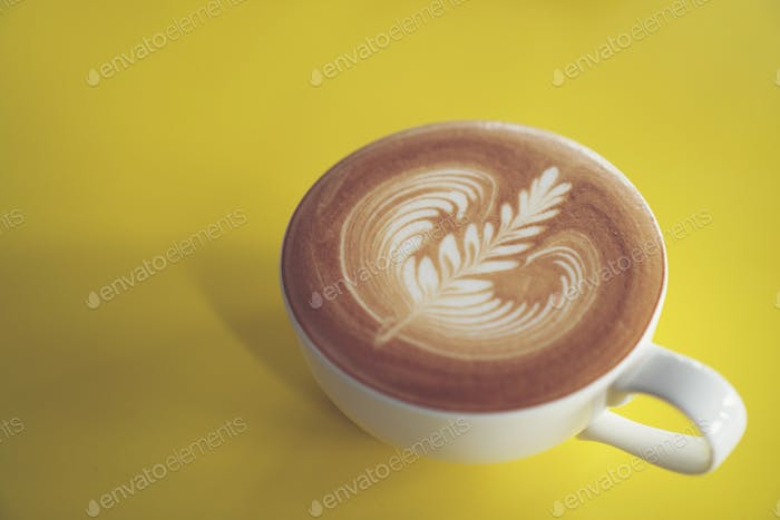 latte art on yellow cafe table, coffee cafe