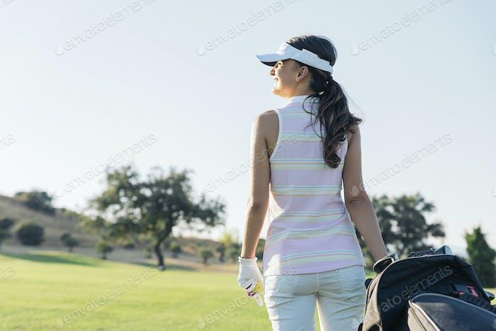 Hübsche junge Frau, die Golf spielt.