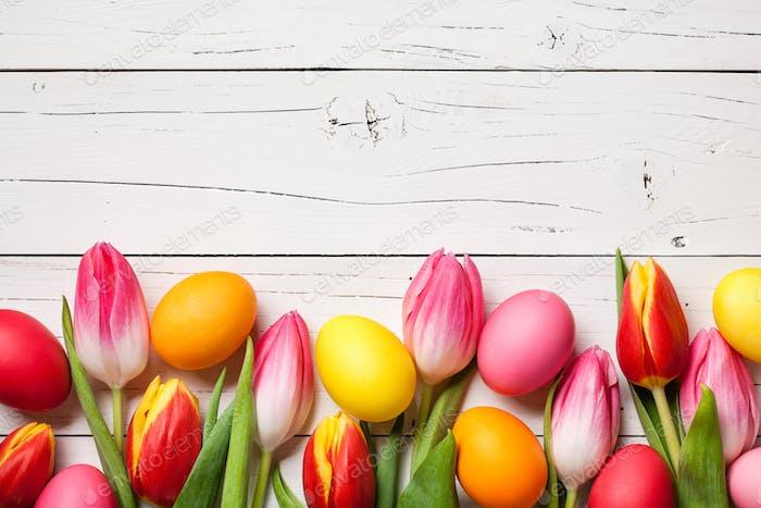 Frische bunte Tulpen und Ostereier auf Holzhintergrund