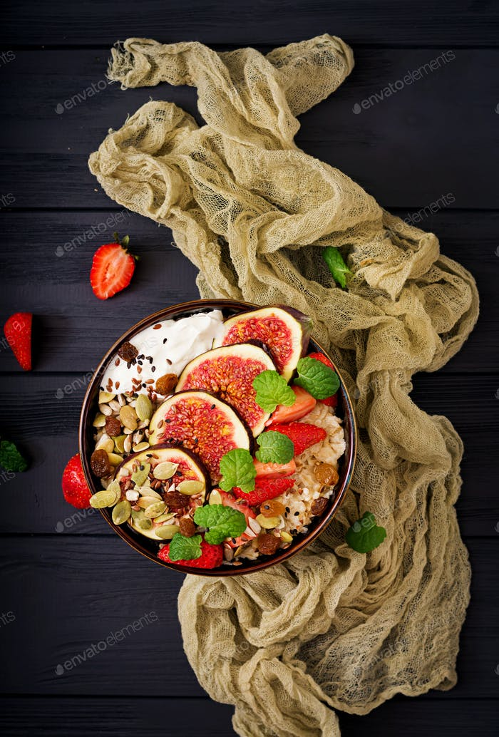 Delicious and healthy oatmeal with figs, seeds, strawberry and yogurt