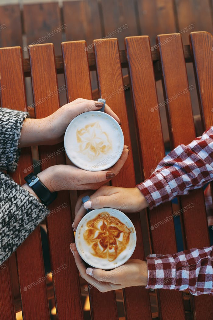 Woman hands with freckles holding cups of coffee